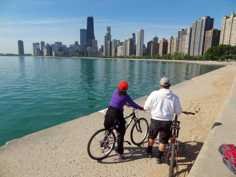 bicyclist along a lake in a city, one of the things to do in Chicago