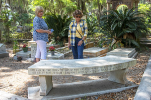 women looking at a grave site of a celebrity, one of the things to do in Savannah