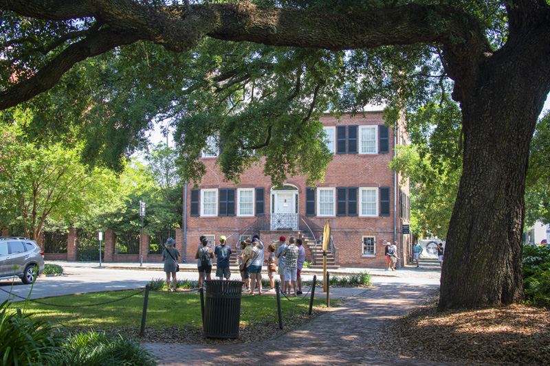 people looking at a historical house, one of the things to do in Savannah