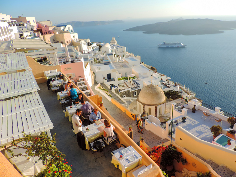 people in a restaurant overlooking a ship in a bay during 24 Hours On Santorini
