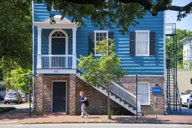 a woman walking by a house painted bright blue