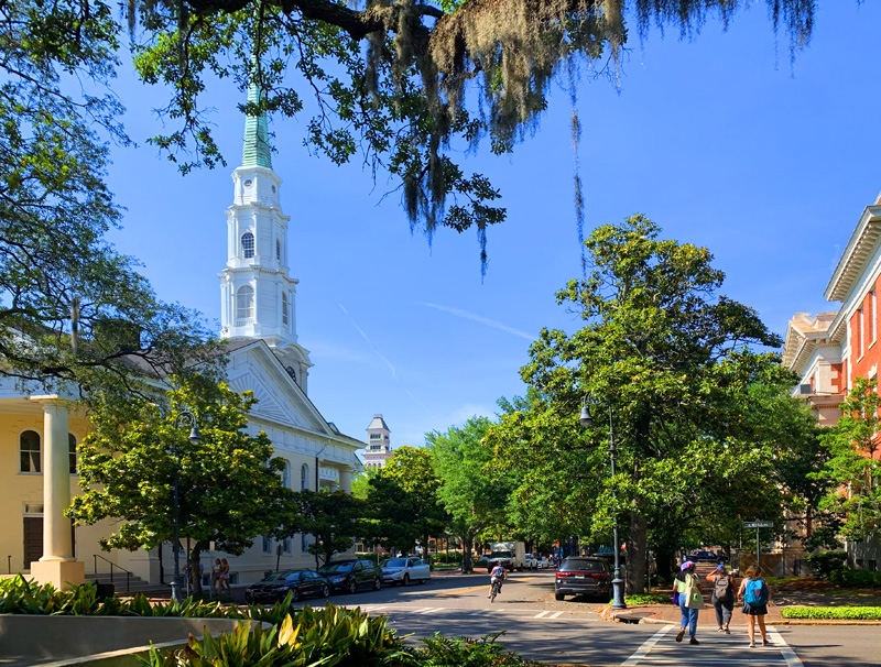 people strolling by a church with a white steeple, one of the things to do in Savannah