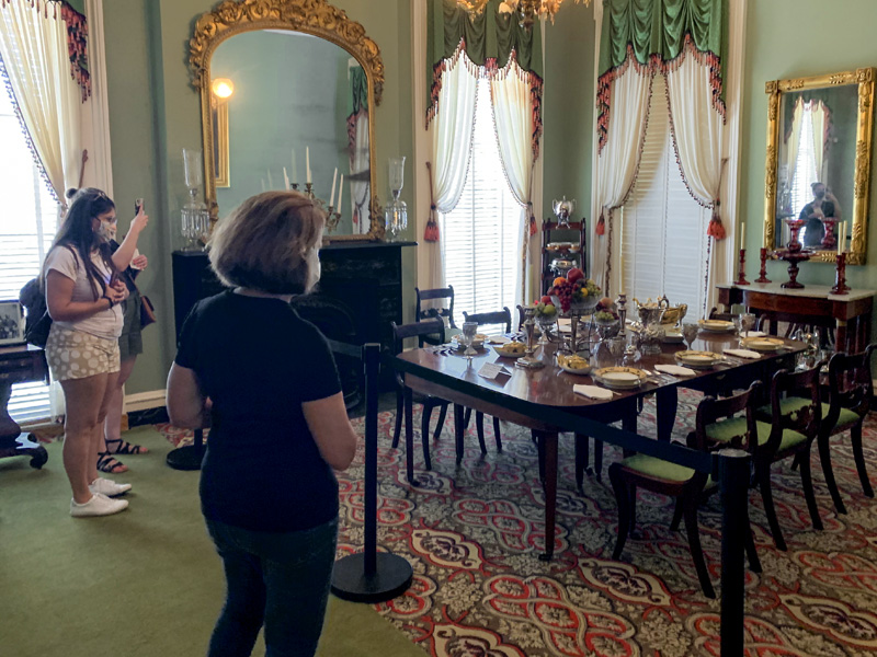 people looking at a furnished room in a museum, one of the things to do in Savannah