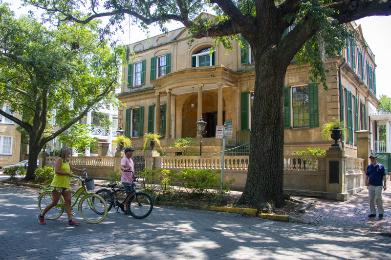 a couple bicycling on a street, one of the things to do in Savannah