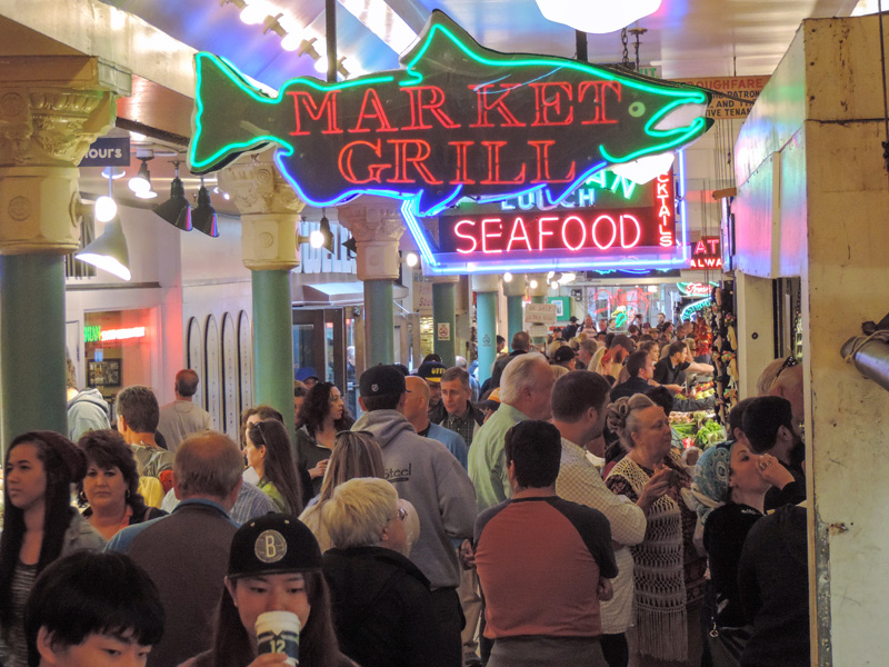 a crowd of people visiting a seafood market - one of the things to do in Seattle