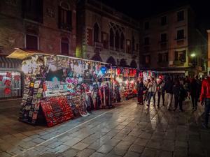 people walking through a night market in Venice