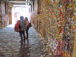 2 women by a wall covered with gum