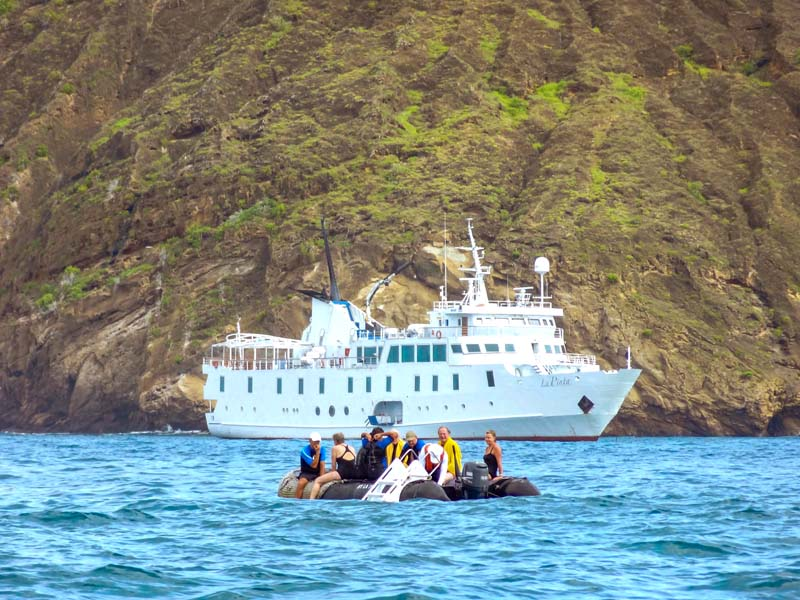 people on a Zodiac going to a ship seen on a Galapagos cruise vacation