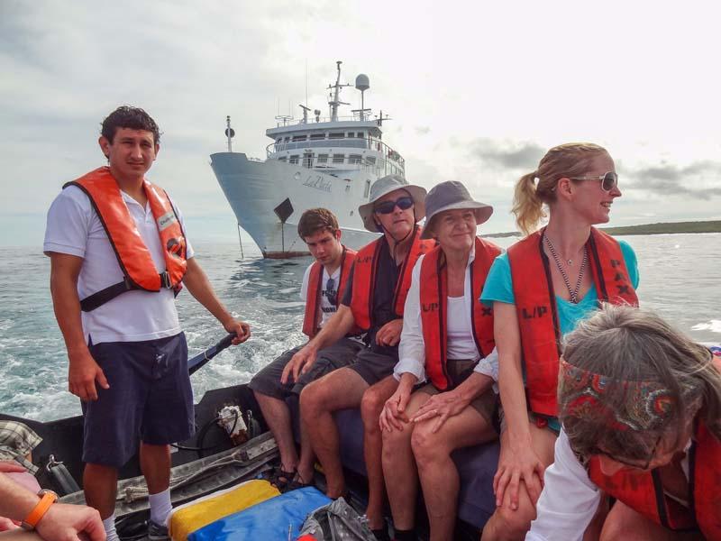 people on a zodiac leaving a ship