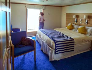 a woman looking at the wind of a ship's stateroom