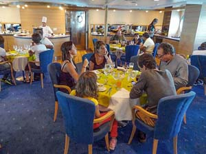 people sitting at a table in a restaurant aboard a ship