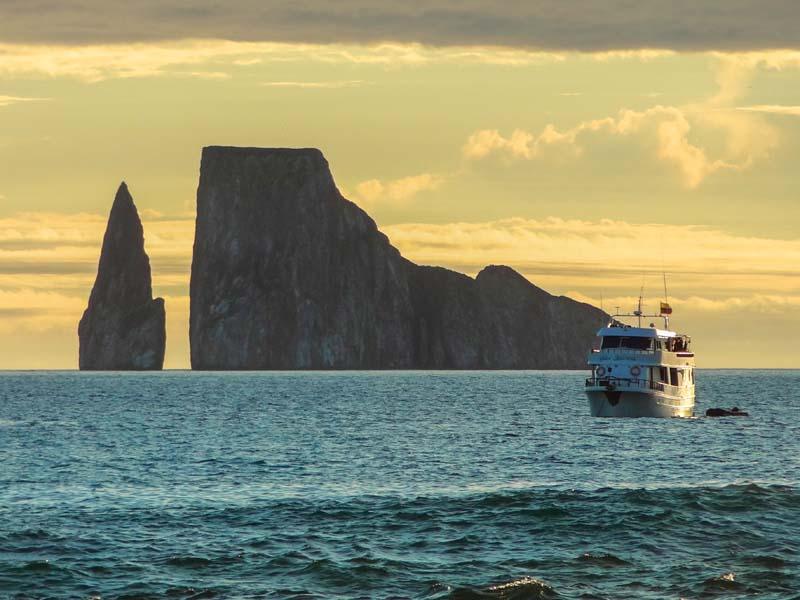 a cruise ship near a huge rock in the ocean
