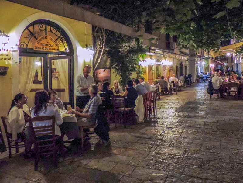 people dining in outdoor restaurants in the evening– one of the things to do in Corfu
