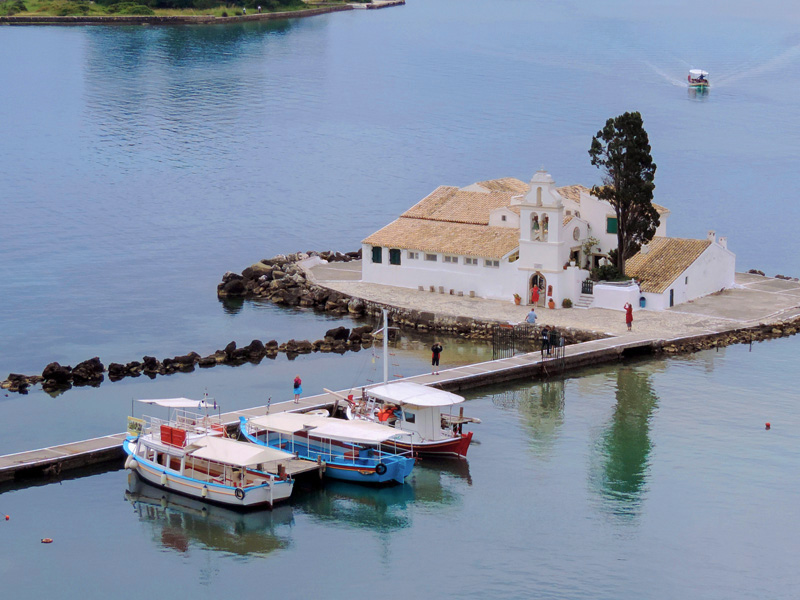 people visiting a monastery on a lake - one of the things to do in Corfu