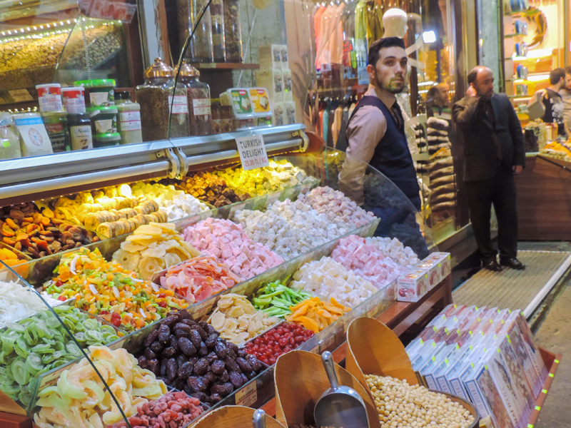 a merchant at a candy display in a bazaar
