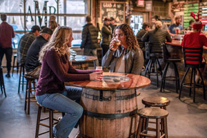 two young women conversing at a table in a bar in the North Carolina High Country