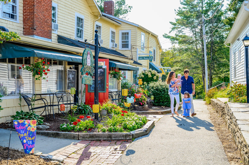 a couple with children walking down a street with cute little stores in the North Carolina High Country