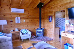 a bedroom with cedar-planked walls at Liscombe Lodge