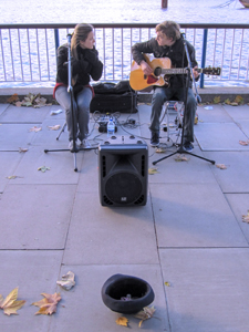 two musicians playing in front of a fence with a hap for tips