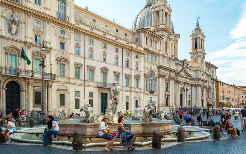 people sitting in front of Baroque buildings on the Piazza Navona