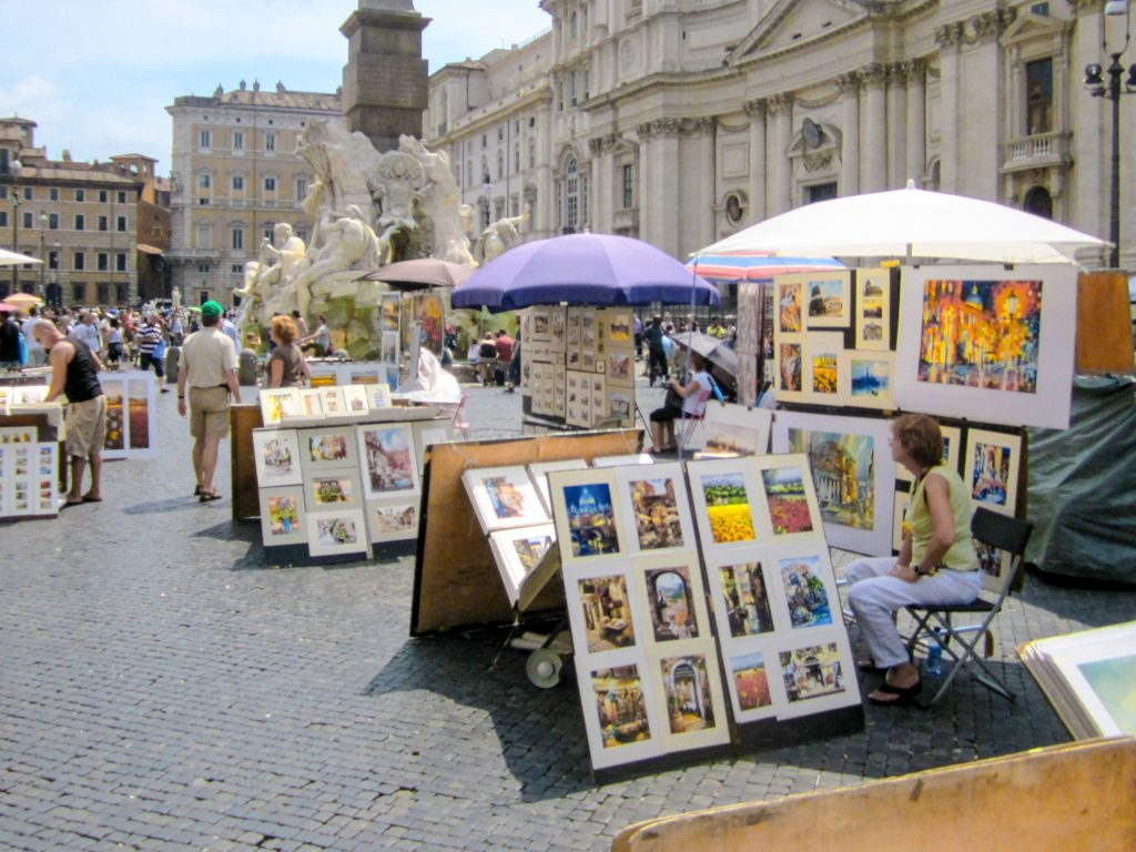artists sitting with the paintings in a large square