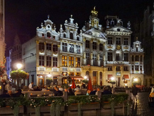 people dining at night by beautiful old floodlit buildings