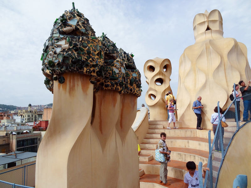 people on a roof by large chimneys - on one of the Gaudi buildings