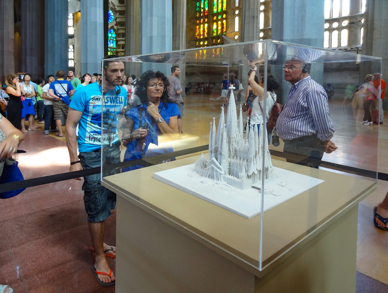 people looking at a model of a cathedral