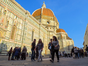 people walking by a large basilica