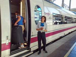 a female conductor helping people aboard on a European train trip