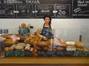 a woman selling bread in a bakery