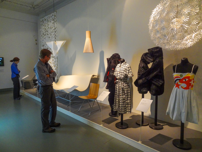 people looking at an exhibit of clothing in a museum, one of the things to do in Helsinki