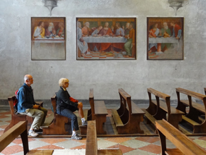 a couple sitting near a fresco of The Last Supper