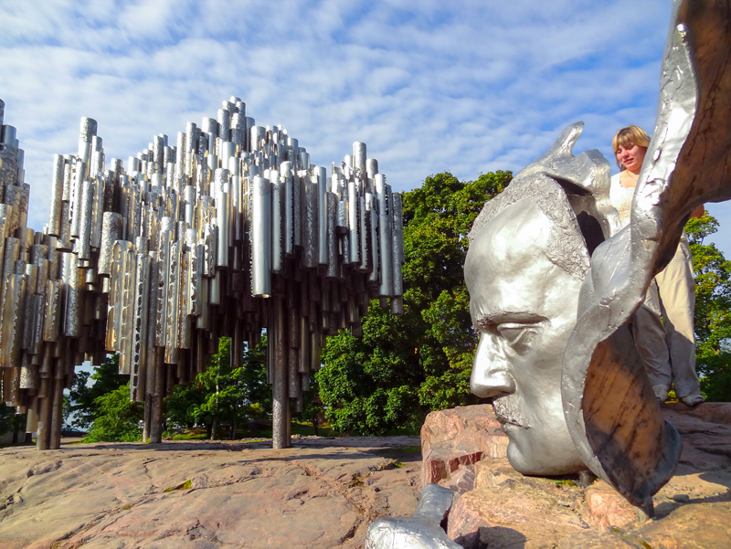 a woman by an outdoor sculpture of the composer Jean Sibelius