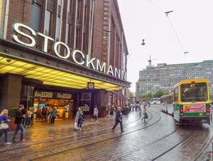 people walking across a street to a tram