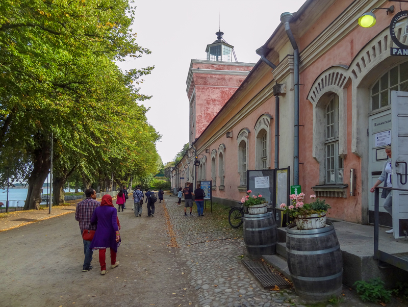 people waling past old buildings in a fortress