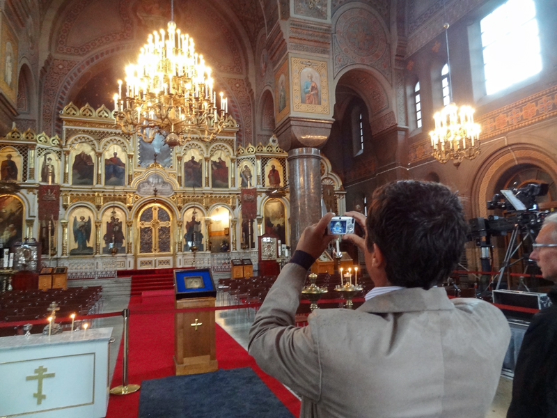 a man taking a photo inside a beautiful, old, ornate cathedral