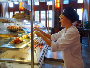 A waitress in a cafe getting dessert for a customer, one of the things to do in Helsinki