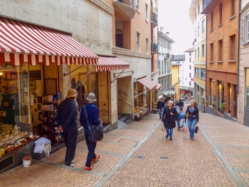 people shopping along a cobblestone street, one of the things to do in Lugano