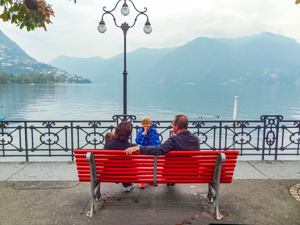 a family sitting by a lake, one of the things to do in Lugano