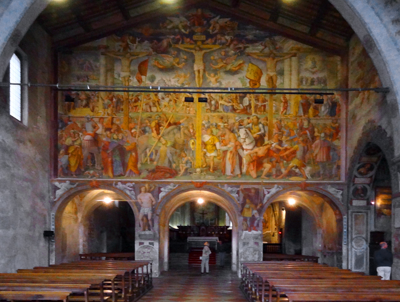 a woman standing beneath a huge fresco in an old church