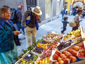 people looking at fruit in a market, one of the things to do in Lugano