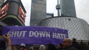 """Protesters hold a large banner reading """"Shut Down Hate"""" in front of Roy Thomson Hall."""