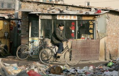 BEIJING, CHINA - JANUARY 2: A cyclist rides past a public telephone booth in a poor slum area on January 2, 2005 in Beijing, China. The Chinese government will focus on reducing poverty over the next four years, in collaboration with the United Nations Development Program. Both sides have invested US$10 million in the project. (Photo by Guang Niu/Getty Images)
