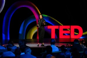 Isha Datar on stage, arm extended, mouth open in mid-sentence. Big, red, lit up letters spelling TED are in the background.