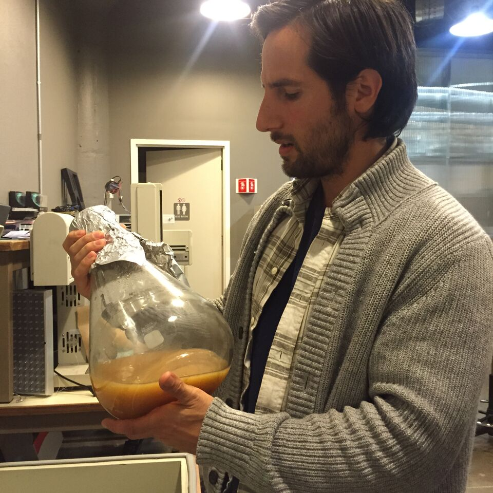 David in the lab holding glass container a yeast culture capable of producing egg white proteins.