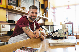 Portrait of male deli owner leaning on counter