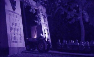 A tractor pulls victims through the gate leading to haunted territory.