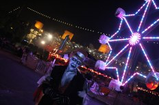 A ghoul haunts the midway near the 2013 Ferris Wheel.
