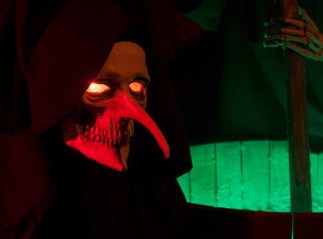 A witch-like figure stirs a cauldron inside the Haunt at Hellizondo.